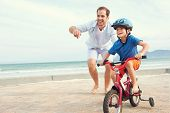 stock photo of father child  - Father and son learning to ride a bicycle at the beach having fun together - JPG