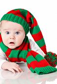 foto of dwarf  - Closeup of cute little baby boy with blue eyes wearing striped Christmas hat with pompon and scarf - JPG