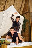 image of straddling  - Young woman straddled happy man and beats him on bamboo bed in bedroom - JPG