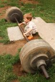 stock photo of lifting weight  - little boy try lift up the barbell in the park - JPG