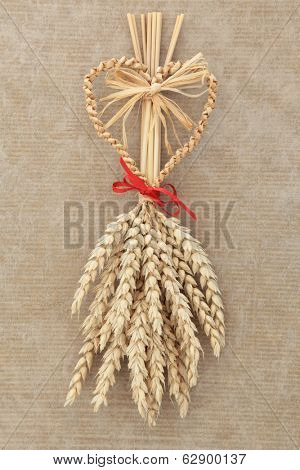 Corn dolly with red bow over old brown paper background.