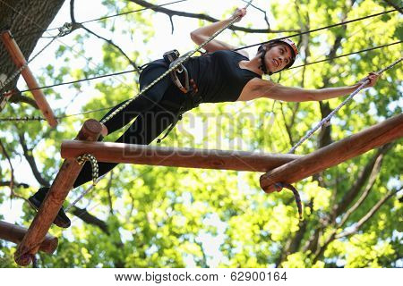 Young caucasian attractive woman climbing in adventure rope park in mountain helmet and safety equipment