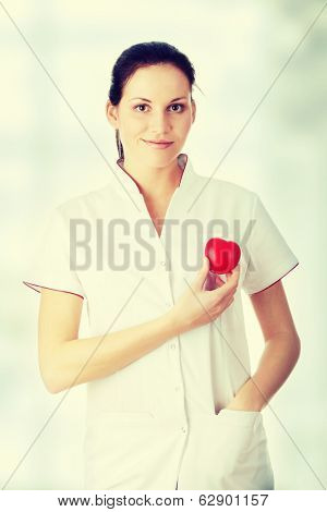 Young nurse with heart in her hand,