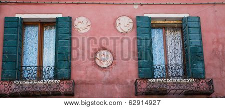 Green Shuttes And Crests On Red Plaster Home