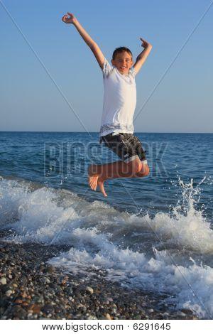 sprung Teenager Boy am Ufer des Meeres