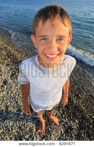 Smiling Teenager Boy Standing On Seacoast