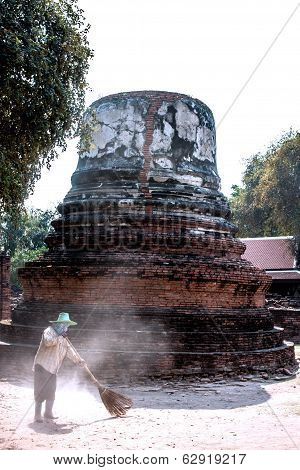 Ayutthaya, Thailand - Feb 05, 2011: Worker Sweeper Cleaning Around Ancient Pagoda With Broom Tool
