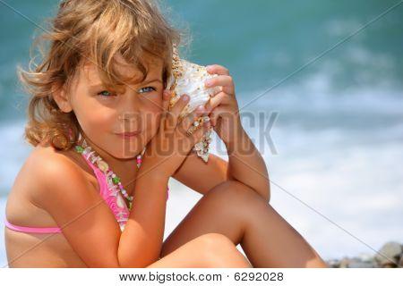 Pretty Little Girl Has Leant Seashell Bowl To An Ear On Seacoast