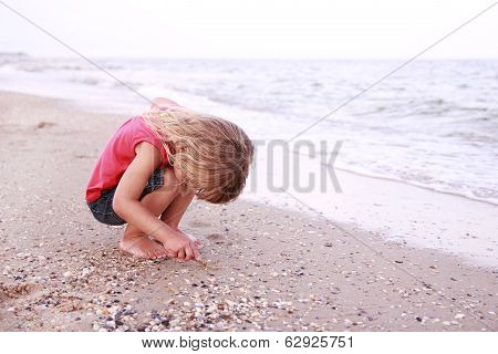 Little Girl Draws A Sun In The Sand On The Seashore