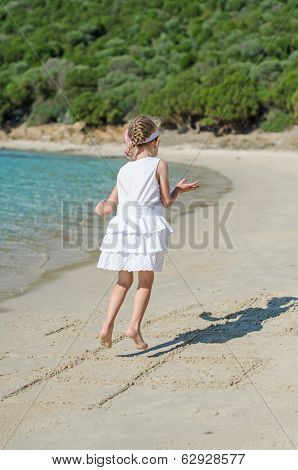 Little Girl Playing Hopscotch Game On The Beach.