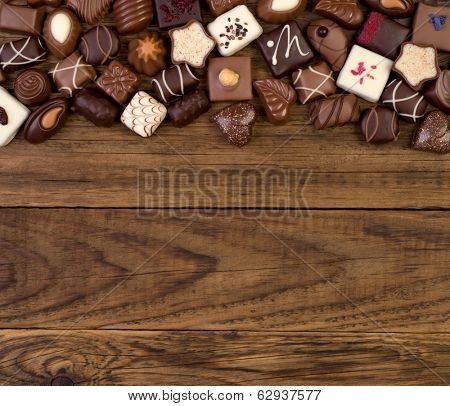 Various chocolates on wooden background with plenty of copy space