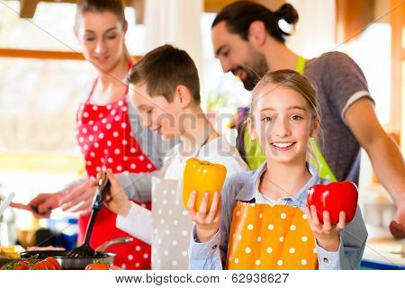 Parents and children, a family, preparing healthy meal in domestic kitchen, having fun