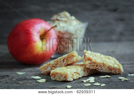 Apple granola barre with fruits and oat in background