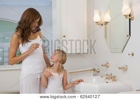Mother and daughter with toothbrushes standing at washbasin in the bathroom