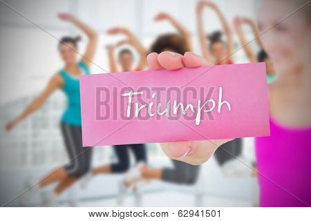 Fit blonde holding card saying triumph against class in gym