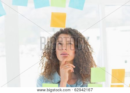 Thoughtful pretty designer looking at sticky notes on window in creative office