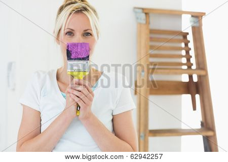 Portrait of a young woman holding paint brush in front of her face at the new house