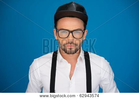 handsome man on blue wearing white shirt and braces , leather hat ,on blue