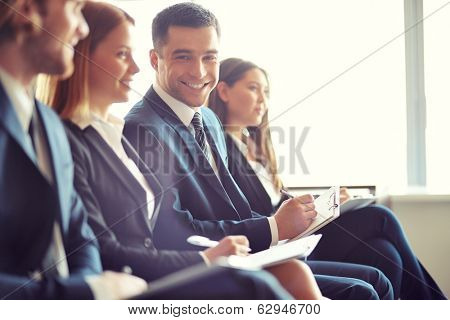 Row of business people making notes at seminar with focus on smiling young man