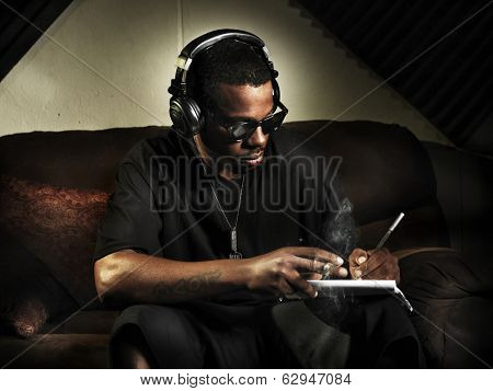 dj writing lyrics on note book in studio