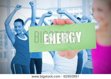Fit blonde holding card saying energy against dance class in gym