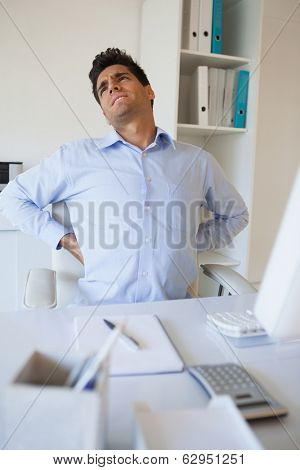 Casual businessman stretching his sore back in his office