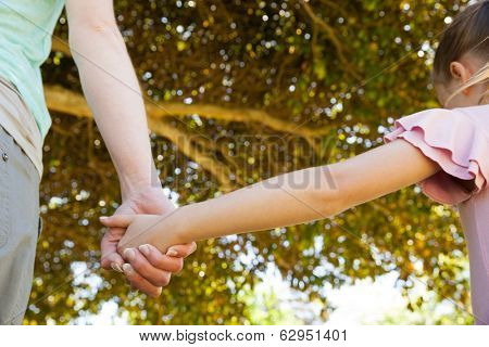 Extreme close-up of a mother holding a hand of her daughter outdoors
