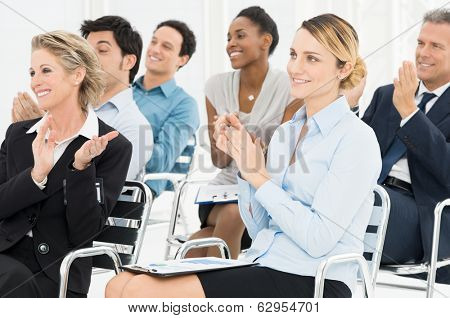Group Of Happy Multiracial Businesspeople Clapping At Seminar
