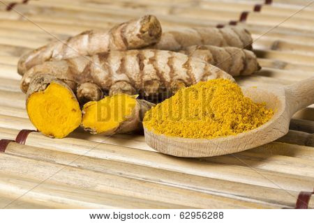 Ground turmeric on wooden spoon and turmeric roots on bamboo mat