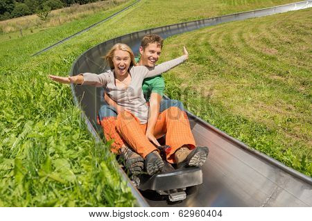 Excited young couple enjoying alpine coaster luge during summer