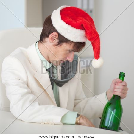 Drunk Man In A Christmas Cap With Bottle Sits At Table