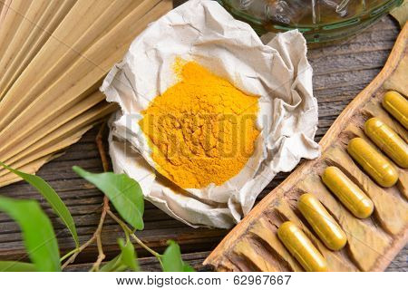Natural herbal tumeric capsules with fresh herb leaves and dry curcumin in paper