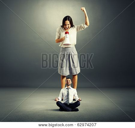 angry woman and calm yoga man over dark background