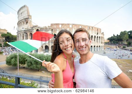 Italy travel couple with Italian flag by Colosseum embracing. Happy tourists lovers on honeymoon sightseeing having fun in front of Coliseum. Love and tourisn concept with multiracial couple.