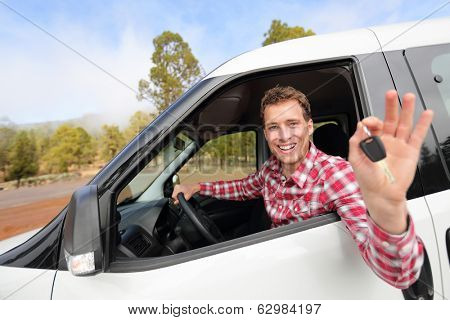 New cars - man driving car showing car keys happy looking at camera. Male driver on road trip in beautiful landscape nature. Focus on model.