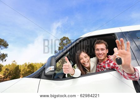 New car - happy couple showing car keys driving having fun on road trip drive in rental car. Happy lifestyle with beautiful young interracial couple outdoors on travel. Man driver and woman passenger.