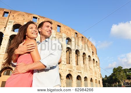 Romantic travel couple in Rome by Coliseum embracing in Italy. Happy lovers on honeymoon sightseeing having fun in front of Colosseum. Love and travel concept with multiracial couple.