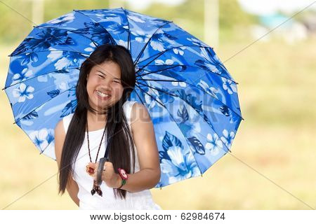 Beautiful young Thai girl under a blue sunshade or umbrella to protect her against the hot summer sun smiling happily at the camera
