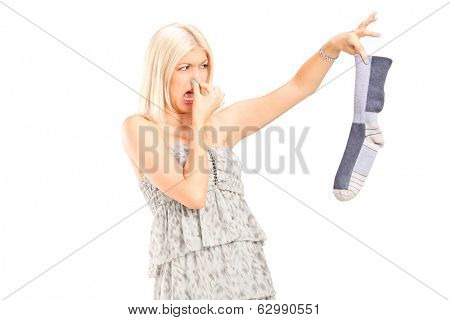 Woman holding a stinky sock isolated on white background