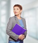 stock photo of 55-60 years old  - attractive woman 50 years old with a folder for documents - JPG