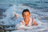 Teenager Boy Swim In Clothes In Sea