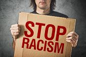 stock photo of stop hate  - Man holding cardboard banner with STOP RACISM message - JPG