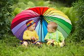 stock photo of rainy season  - cute little children under colorful umbrella outdoors - JPG
