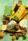picture of cheese platter  - British and French cheese on a wooden board on a green background cheese knives nuts and basil leaves