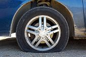 stock photo of slit  - close up of a flat tire of a blue car centered on gravel road - JPG