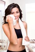 image of transpiration  - Fitness woman wiping sweat with a towel