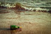 Vintage retro hipster style travel image of message bottle on beach sand in waves with grunge textur