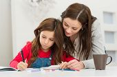 stock photo of cute innocent  - Happy Young Mother Helping Her Daughter While Studying At Home - JPG