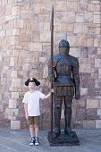 Boy stands with a statue of a medieval warrior.