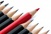 stock photo of rebel  - One red pencil standing out from the row of black pencils - JPG
